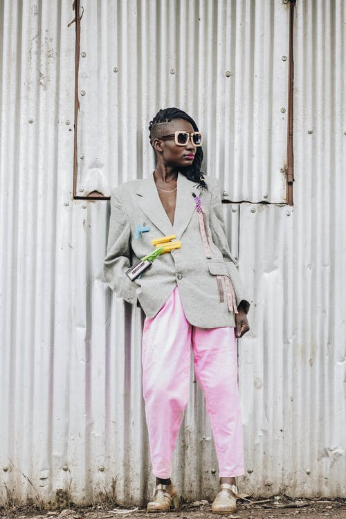 Man in Gray Blazer and Pink Pants Wearing Black Sunglasses Standing Beside White Wooden Wall