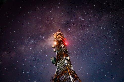 Transmission tower under starry night sky