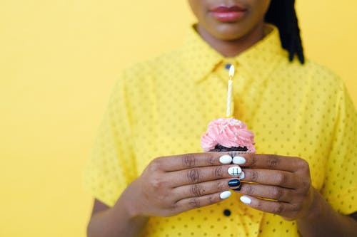 Woman in Yellow and White Polka Dot Shirt Holding Pink Flower