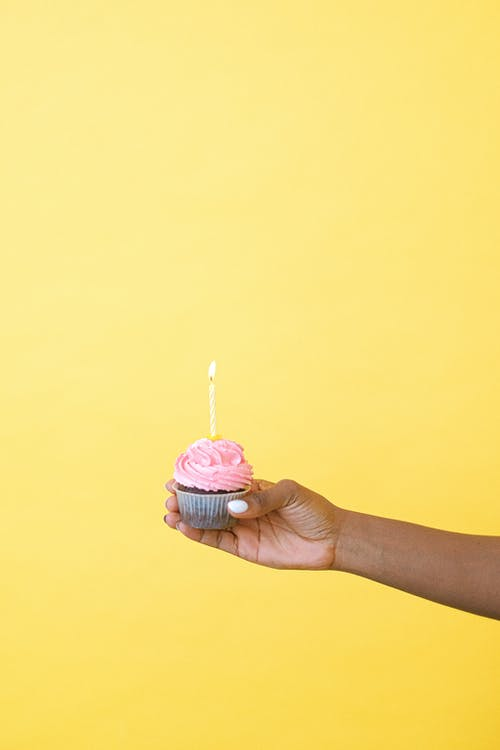 Person Holding Cupcake With Pink Icing