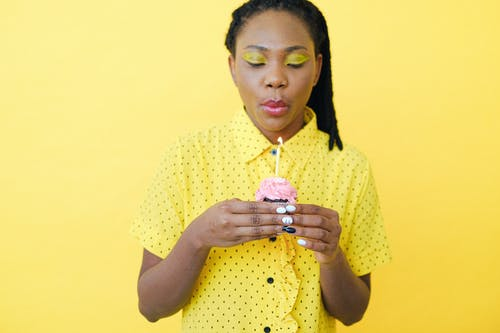 Woman in Yellow and White Polka Dot Shirt Holding Lighted Candle