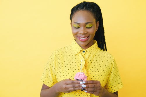 Smiling Woman in Yellow and White Polka Dot Button Up Shirt Holding Clear Glass Cup