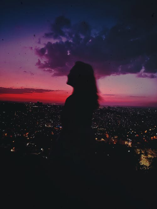 Woman standing against night city and sky