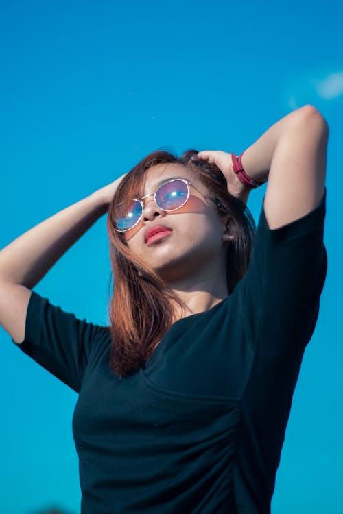 Woman in Blue Crew Neck T-shirt Wearing Aviator Sunglasses