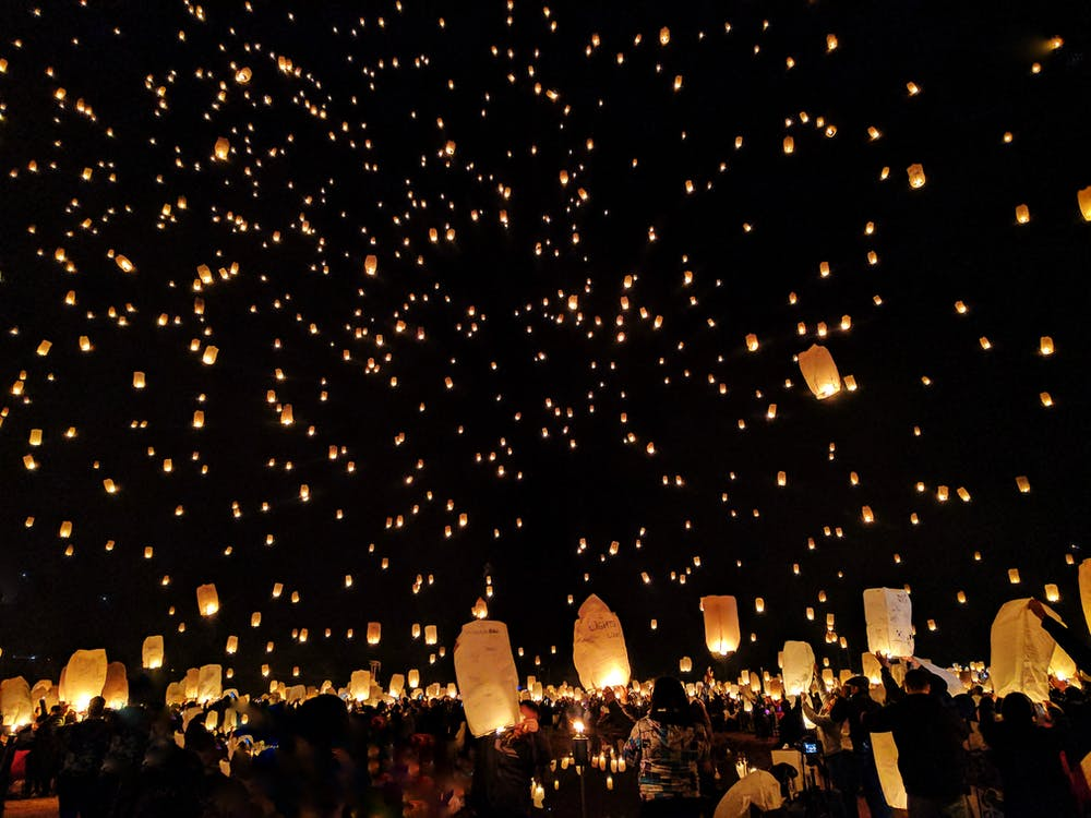 Group of People Throwing Paper Lantern on Sky during Night