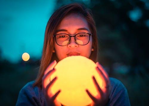 Woman in Black Framed Eyeglasses Holding Round Fruit