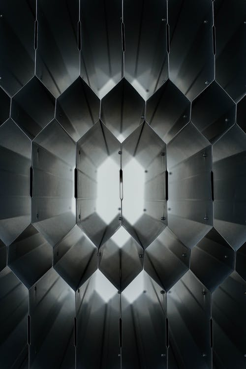 Abstract background of symmetrical metal construction illuminated with daylight