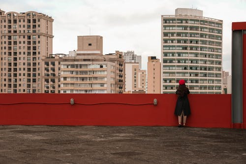 Back view of anonymous female in outerwear contemplating contemporary multistory residential buildings while standing on shabby fenced roof in city