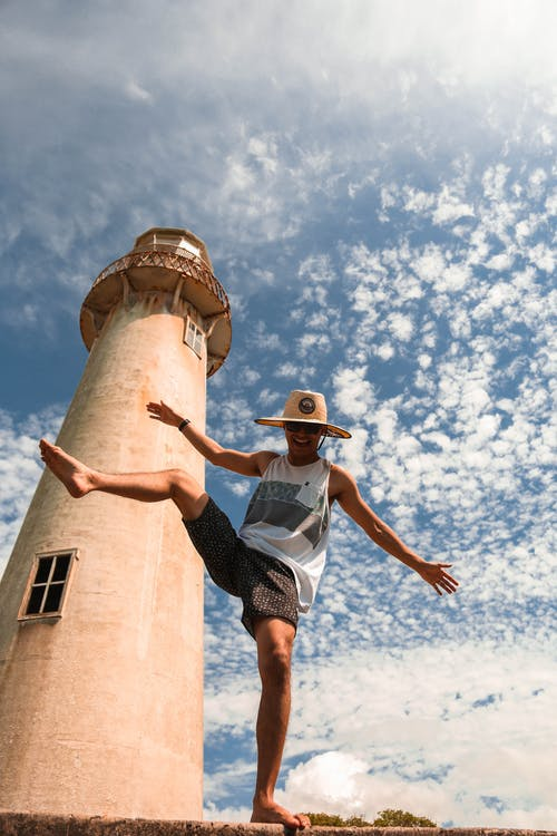 Unrecognizable tourist dancing near old lighthouse under cloudy sky