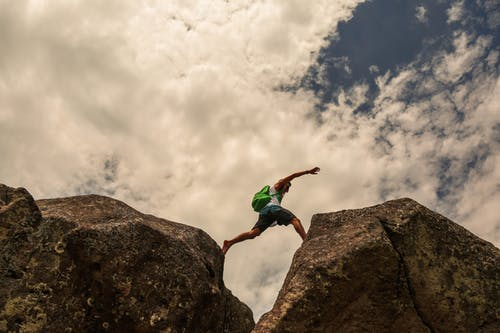 From below side view of fit anonymous traveler with backpack leaping bristly rocks under sky in clouds during trip