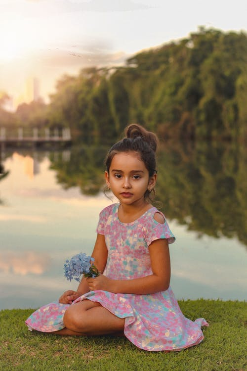 Charming girl with blooming flowers resting on grass near pond