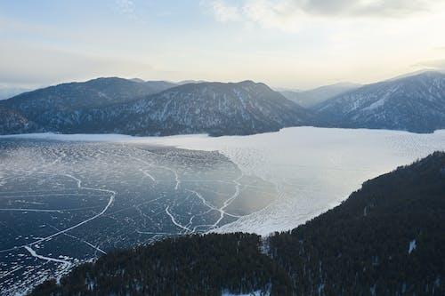 Snowy mountains on coas of frozen lake in winter