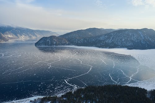 Wooded mountains on shore of frozen lake in winter