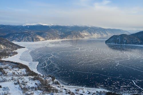 Snowy mountainous on coast of frozen lake in winter