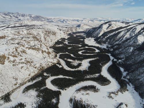 Riverbed of frozen river in mountainous terrain in winter