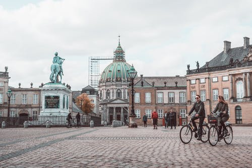 Old church facade near square with people riding bicycles