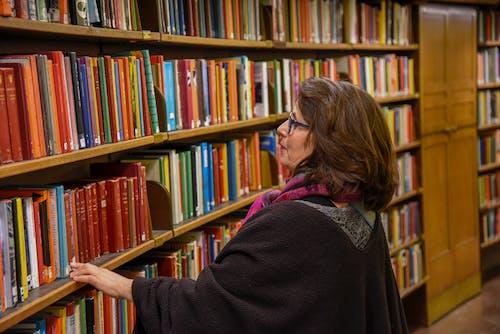 Woman choosing book in public library