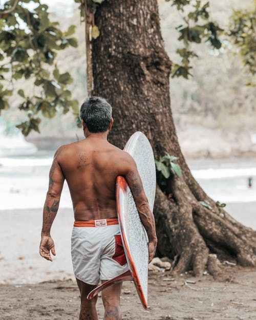 Topless Man Holding White Surfboard Walking on Brown Sand