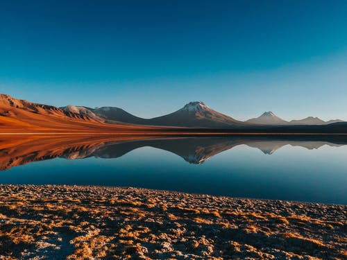 Lake reflecting bright mountains under blue sky