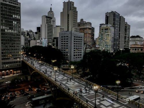 Pedestrian bridge near skyscrapers in night city