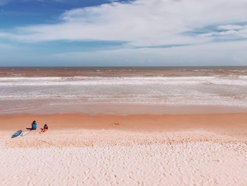 Unrecognizable tourists lying on sandy beach near ocean