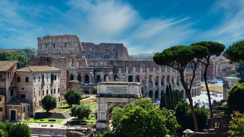 From above of aged masonry Colosseum and ancient arch near trees under bright blue cloudy sky in Italy