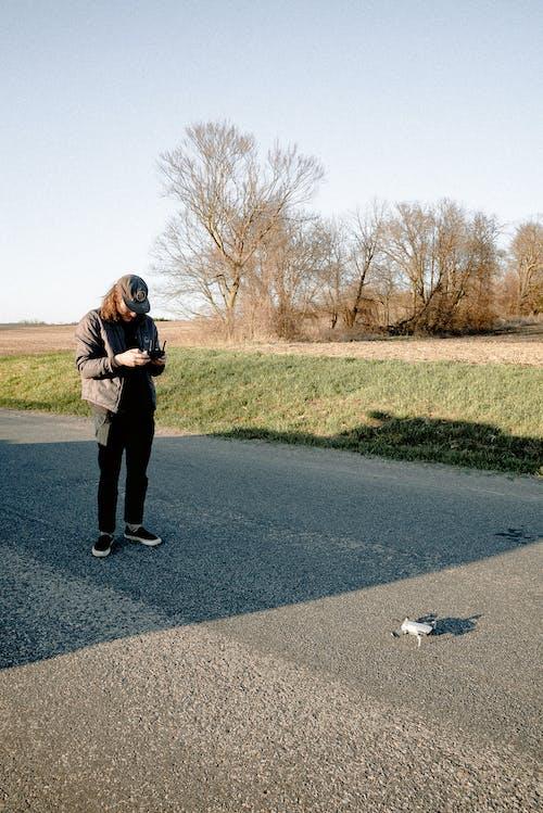Woman in Black Jacket and Black Pants Standing on Gray Asphalt Road