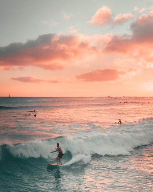Man Surfing on Sea Waves during Sunset