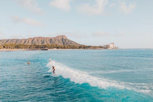 Person Surfing on Sea Near Mountain