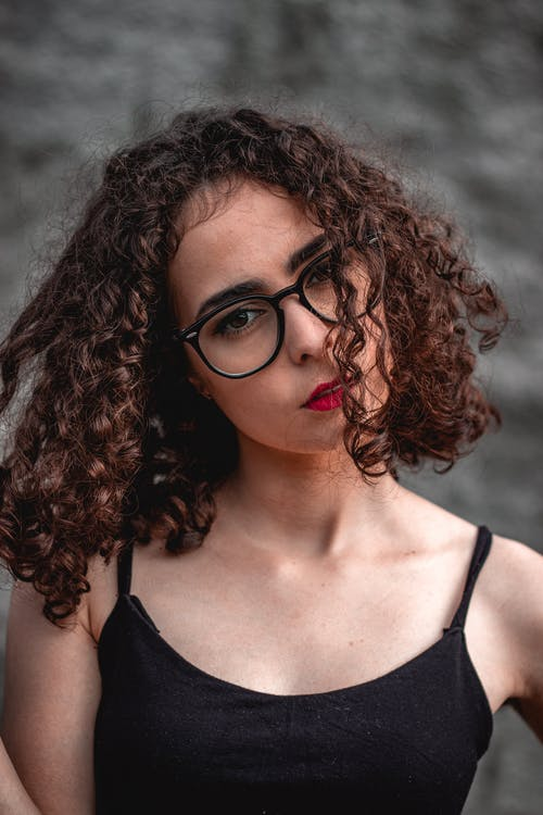 Portrait of a Brunette with Curly Hair Wearing Black Eyeglasses