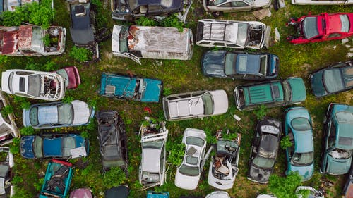 Car dump located on greenery in summer day