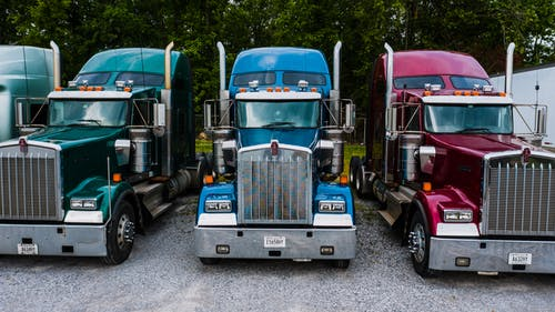 Vintage classic trucks of different colors parked in row on asphalt road against green trees