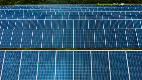 Contemporary installation of solar panels mounted on field in environmental friendly solar power station