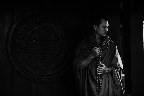 Black and white calm pensive Buddhist monk with beads wearing traditional clothes standing near ornamental temple wall with round caved drawing and looking down in thoughts