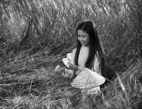 Carefree Asian girl resting on grassy field