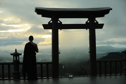 Unrecognizable monk standing near sacred Torii Gates of Buddhist sanctuary
