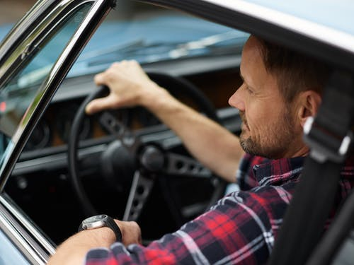 From above back view of confident male with short beard and mustache in plaid shirt sitting in automobile with hand on steering wheel