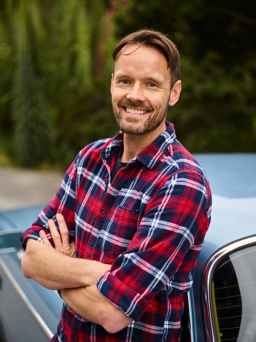 Happy male driver leaning on car and looking at camera