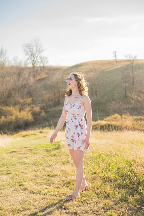Delighted young woman singing in sunny nature