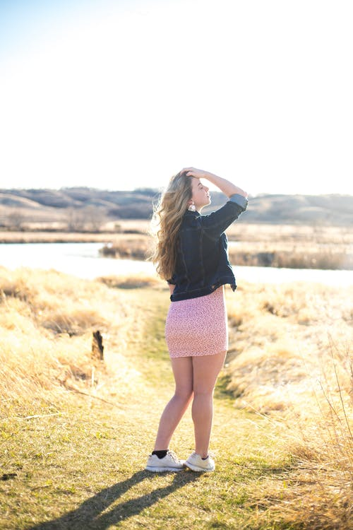 Back view full length content relaxed female in mini summer dress standing on grassy lawn and touching hair while enjoying sunny weather