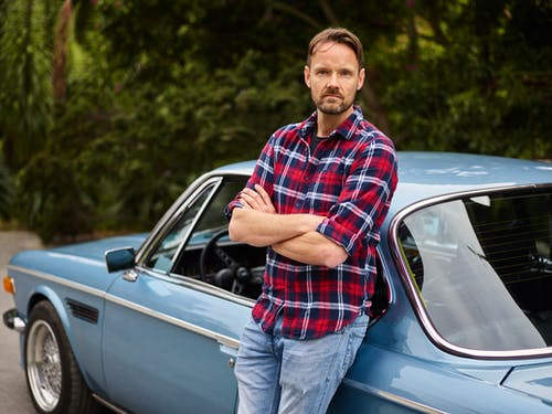 Calm man standing with folded arms near old car