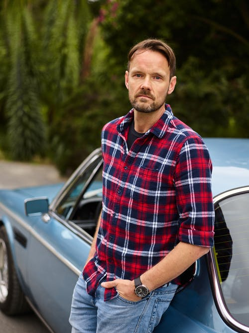 Adult pensive bearded guy in wristwatch standing with hand on pocket leaned on blue retro car near green trees in countryside and looking at camera