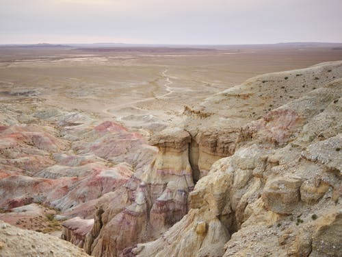 Scenic view of shabby uneven rocky formations covered with shade of pink color near plain on horizon under cloudy sky in afternoon