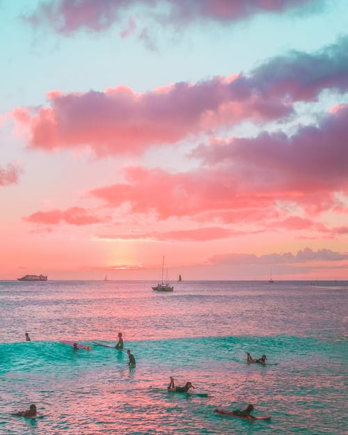 People Swimming in Sea during Sunset
