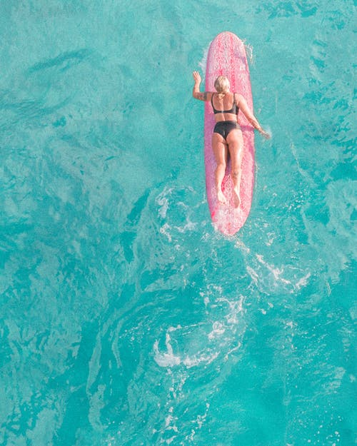 Woman in Pink Bikini Lying on Pink Inflatable Float on Water