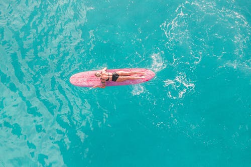 Woman in Pink and White Bikini Lying on Pink Surfboard on Water