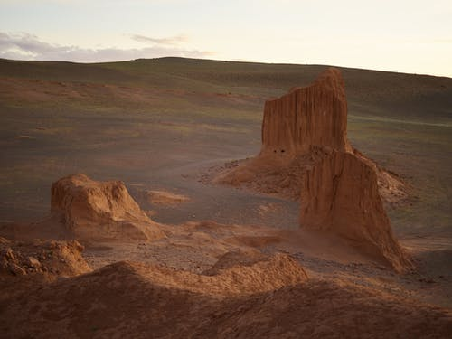 Majestic aerial view of red cliffs in empty desert valley under bright sky in coming evening