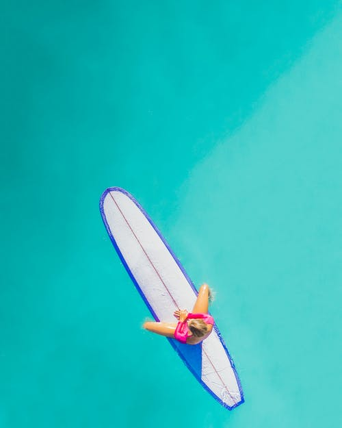 Man in Blue and White Board Shorts Riding White and Blue Surfboard