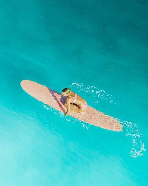 Woman in Black Bikini Lying on Brown Surfboard on Water