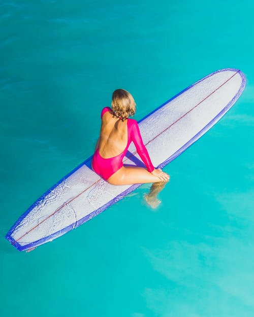 Woman in Red Bikini Top and White and Blue Surfboard in Water